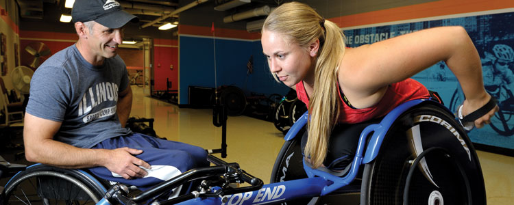 Using specialized gloves she made with a 3D printer, Arielle Rausin pushes the pegs of her racing chair alongside her Illinois wheelchair track coach, Adam Bleakney.