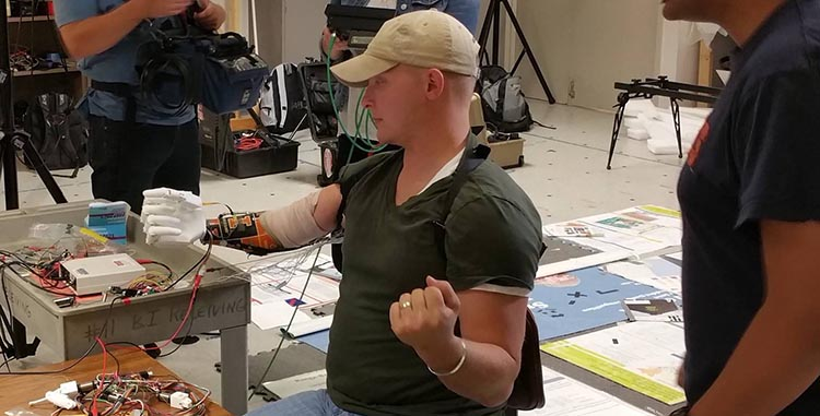 Retired Sergeant Garrett Anderson, who lost his right arm in Iraq in 2005 when a roadside bomb detonated under the truck he was driving, tests a prototype of the prosthesic arm with Aadeel Akhtar, an M.D./Ph.D. student in Beckman's Artificial Intelligence Group.