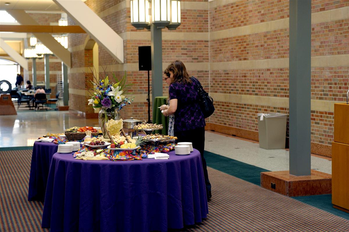Guests browse food at a reception in the atrium of the Beckman Institute.