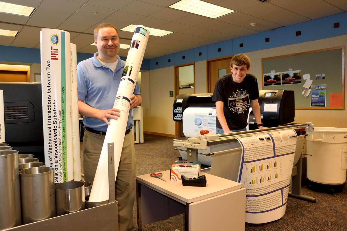 An Internet Technology Services employee helps a student print a poster