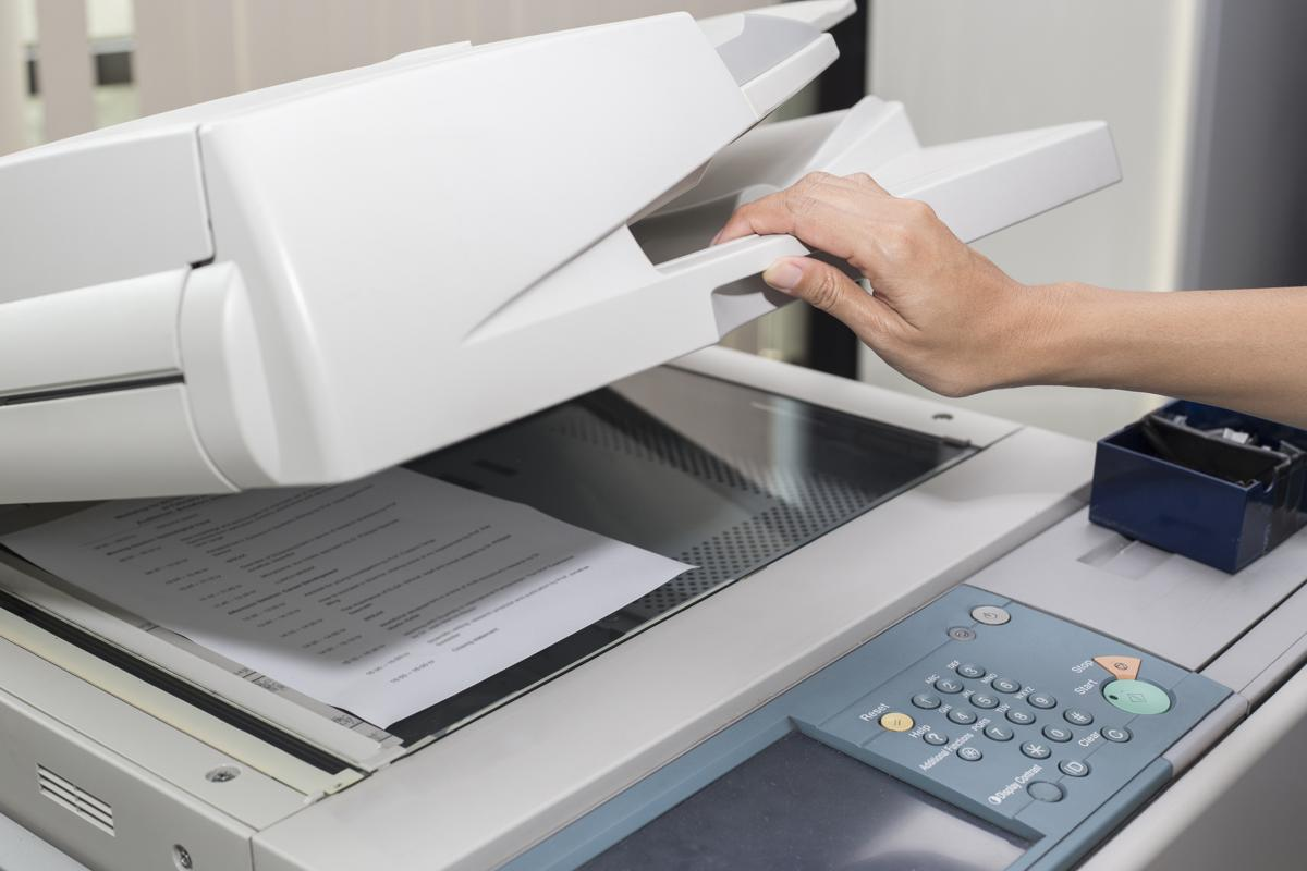 A woman's hand is closing a copier with a piece of paper on the glass