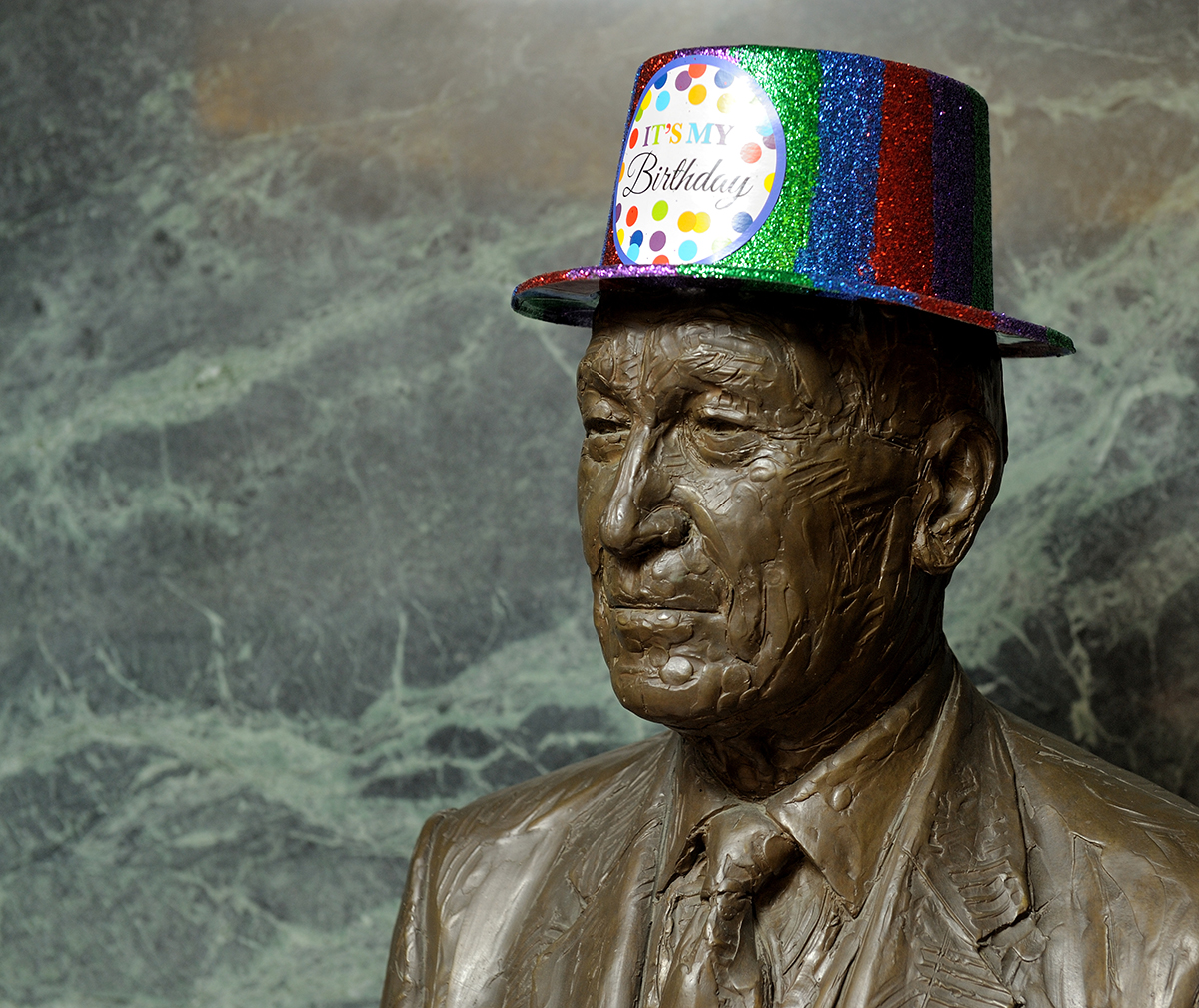 "In honor of events planned around Arnold Beckman's birthday on April 10, hissculpture (statue) at the Beckman Institute wears a green, blue, red top hat with ""It's My Birthday"" on the front."