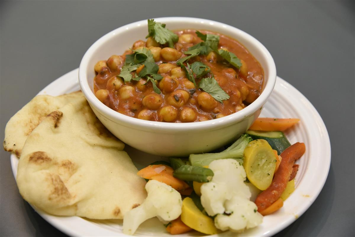 A bowl of Chana Masala, served with naan and mixed vegetables.