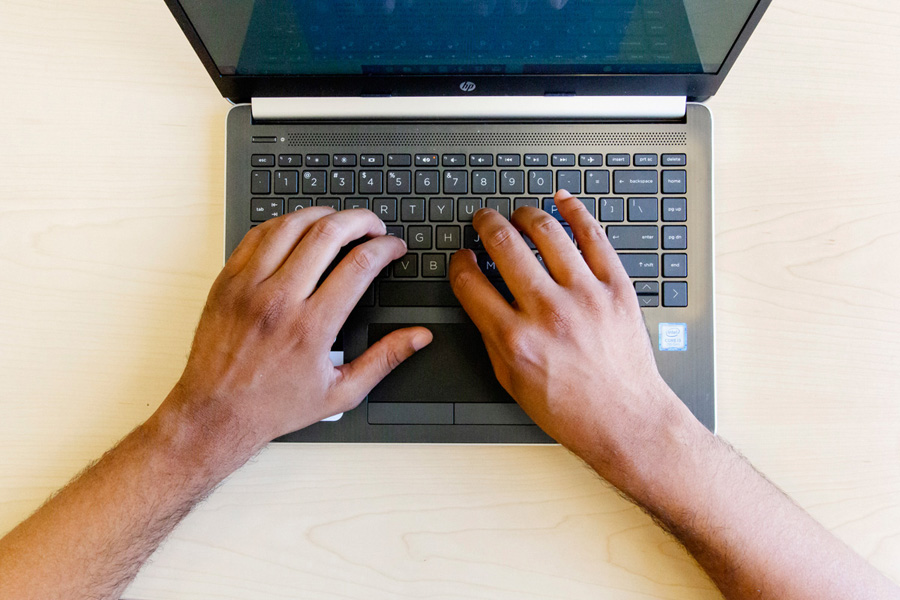 aerial view of a laptop with a person's hands poised on the keyboard