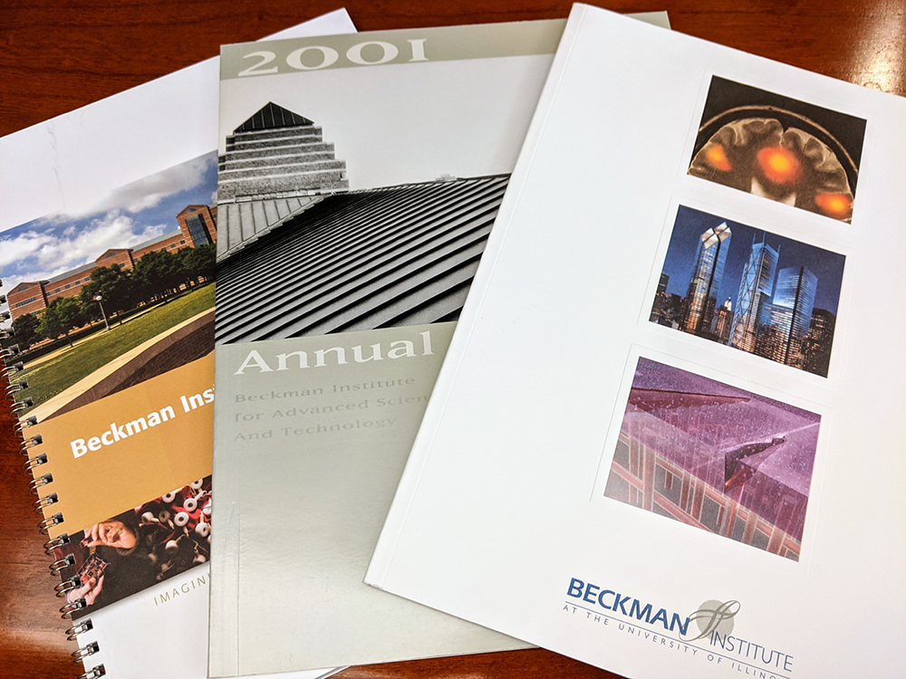 A photo of several annual reports spread out on a wood tabletop.