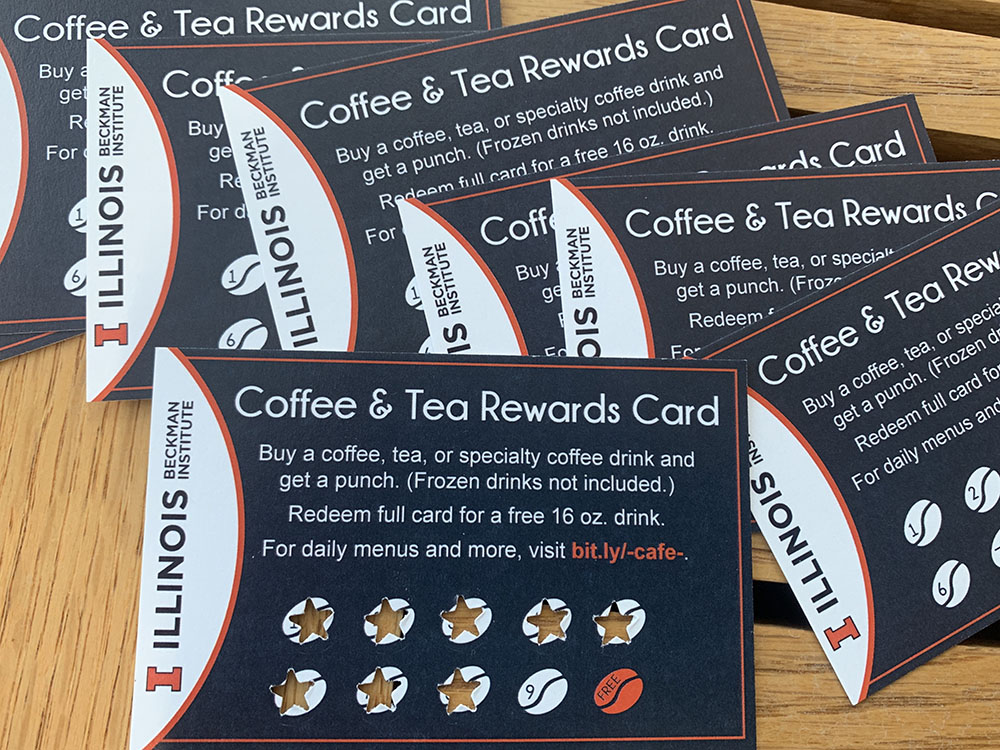 A group of reward punch cards for the Beckman Cafe spread on a wood table top.
