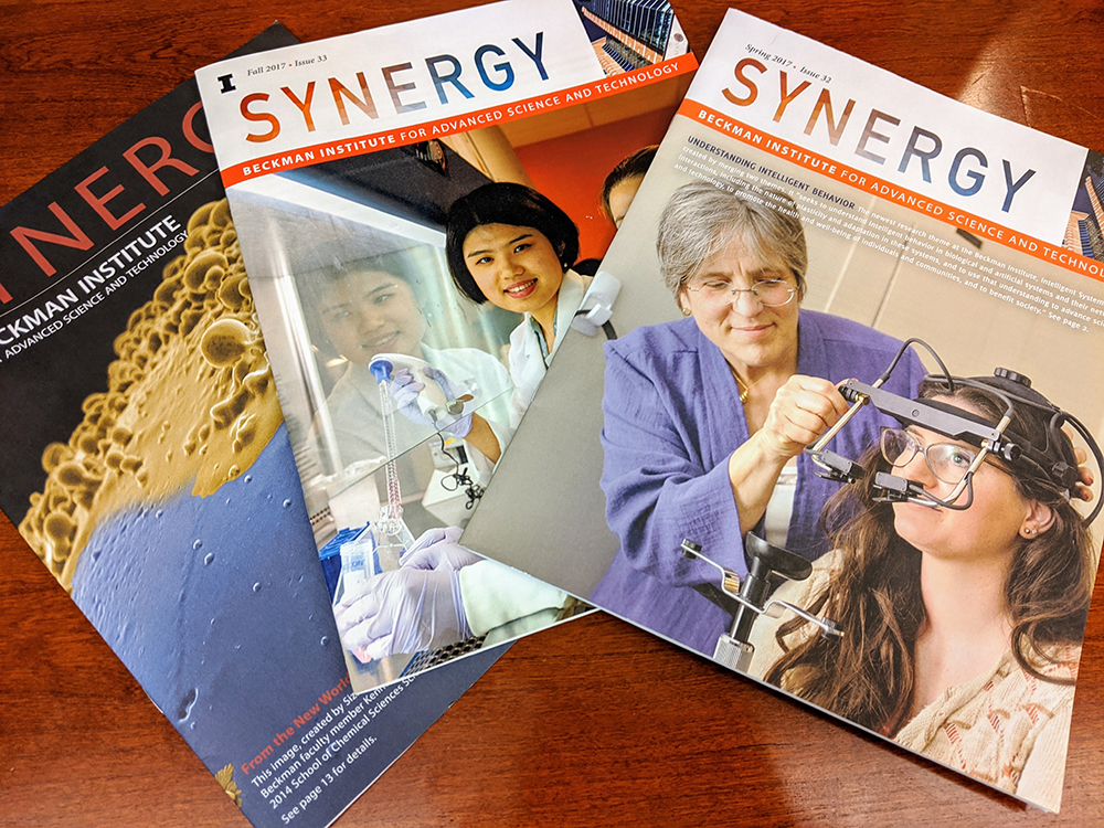 A photo of several covers of Beckman's Synergy magazine on a wood tabletop.