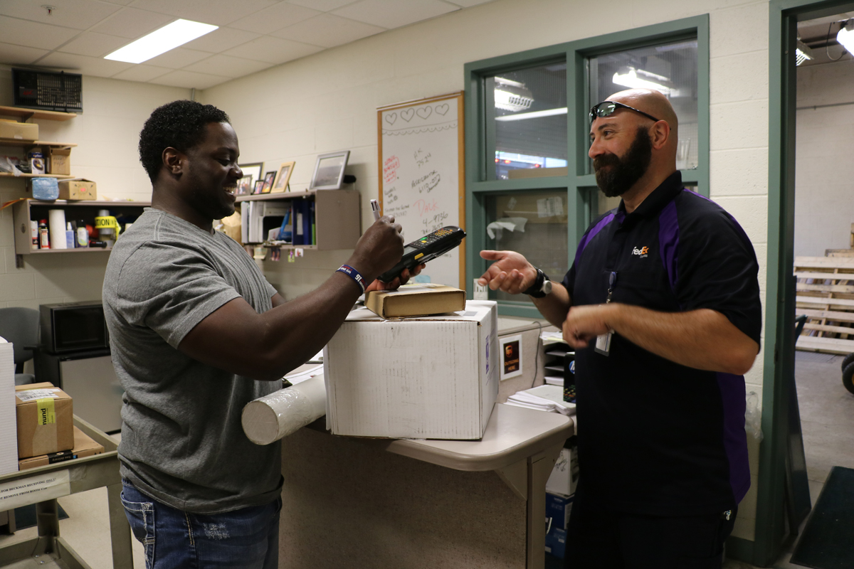 Beckman Shipping and Receiving employee signs for packages from a FedEx employee at the Beckman Institute.