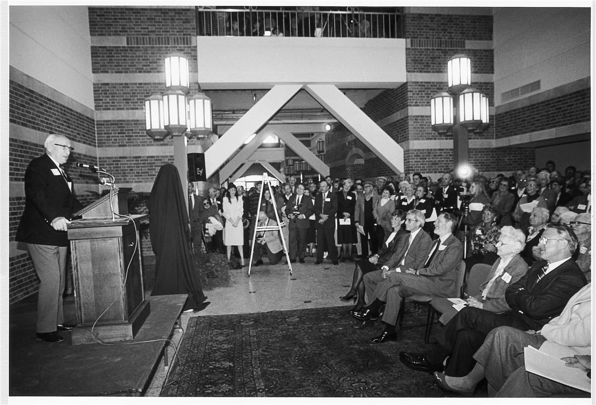 Arnold Beckman addresses a crowd in the atrium of the Beckman institute from a podium