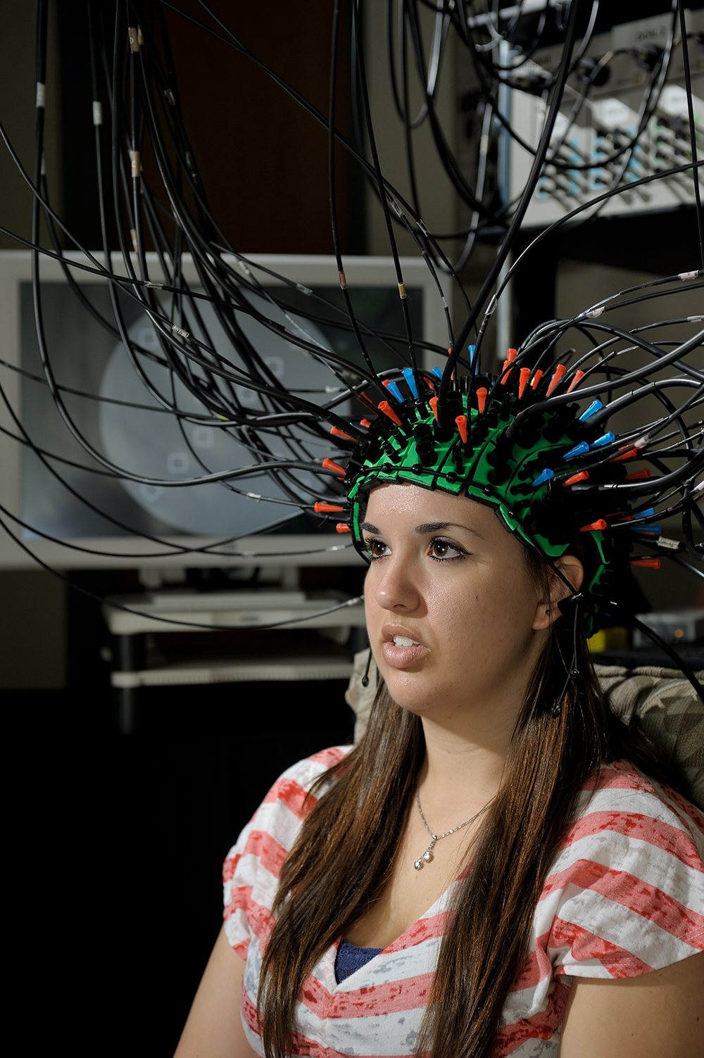 A student wears a cap connected to wires, the Pulse-DOT imaging technique.