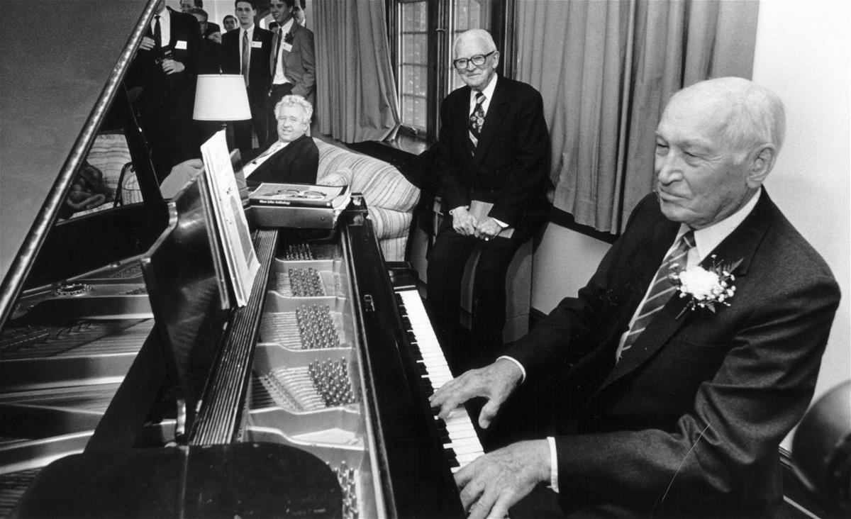 Arnold Beckman plays piano at the Delta Upsilon house on April 6, 1989. His college friend, Seely Johnston, looks on. The event was a part of the inauguration of the Beckman Institute