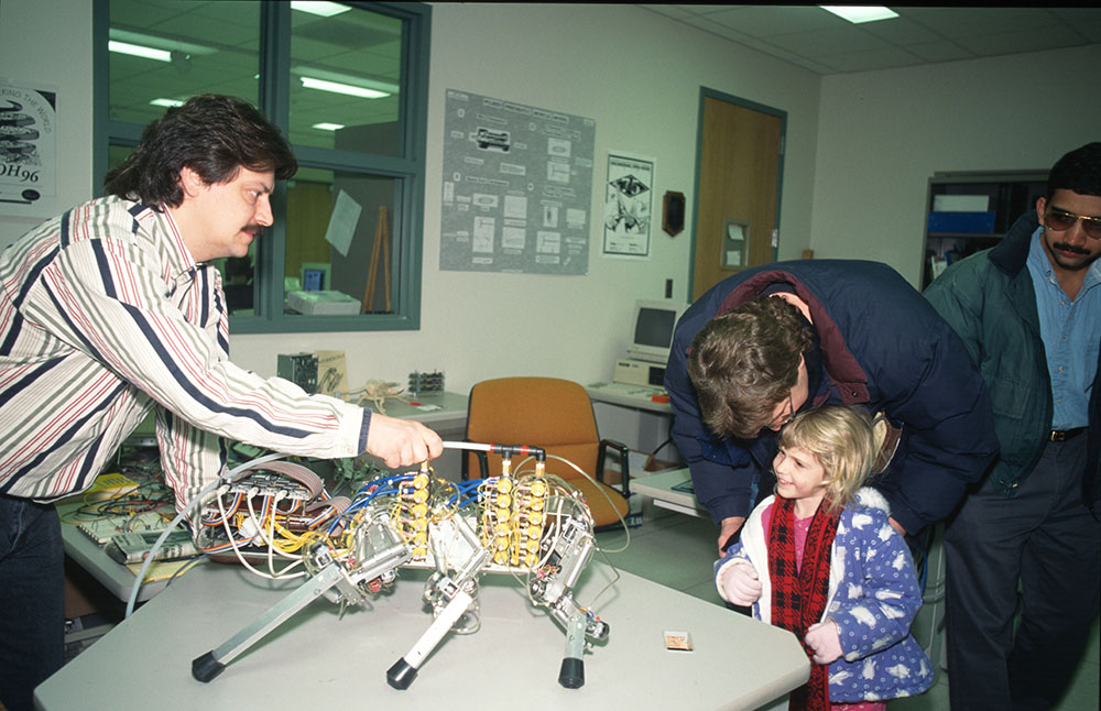 John Hart demonstrates a cockroach robot Beckman's first Open House in 1997.