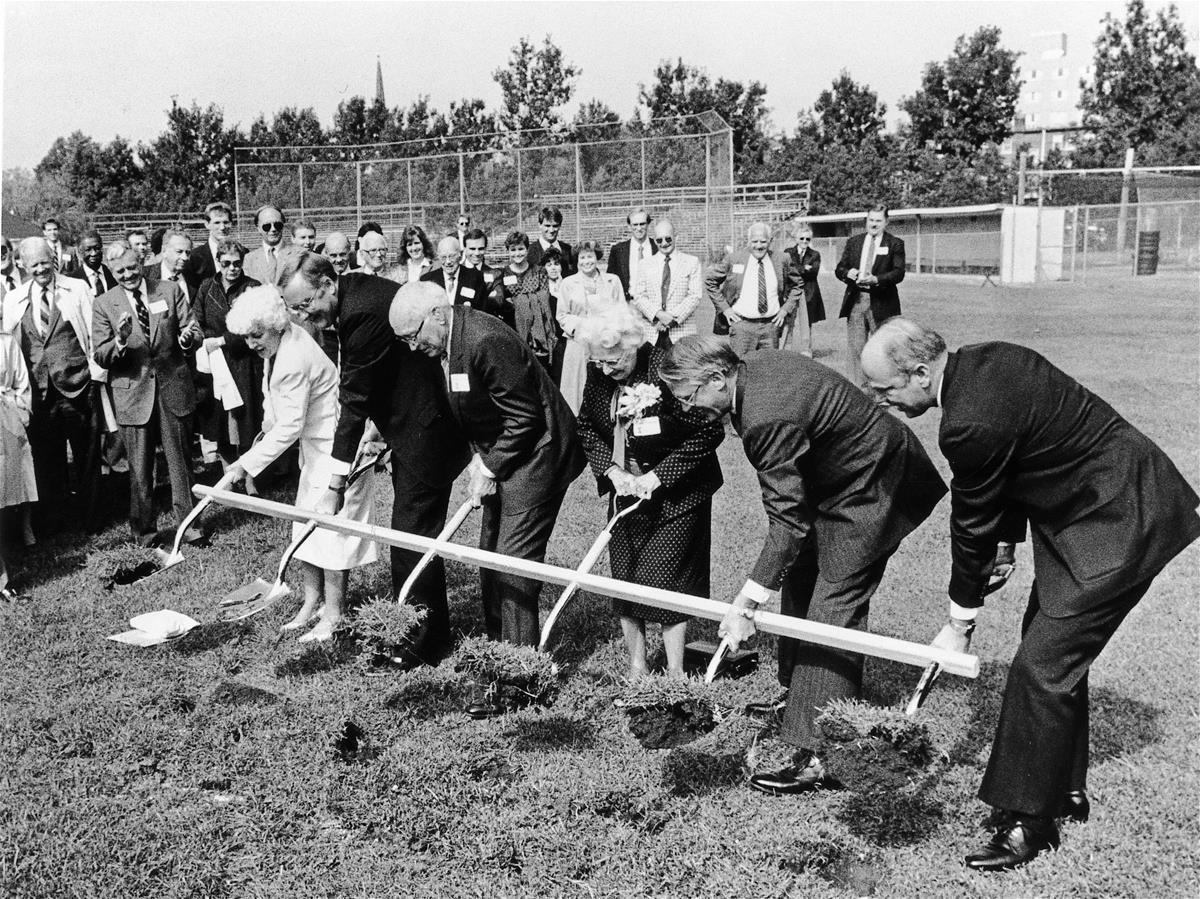 A group of people hold a connected shovel as they break ground on the Beckman Institute at the University of Illinois at Urbana-Champaign (UIUC)