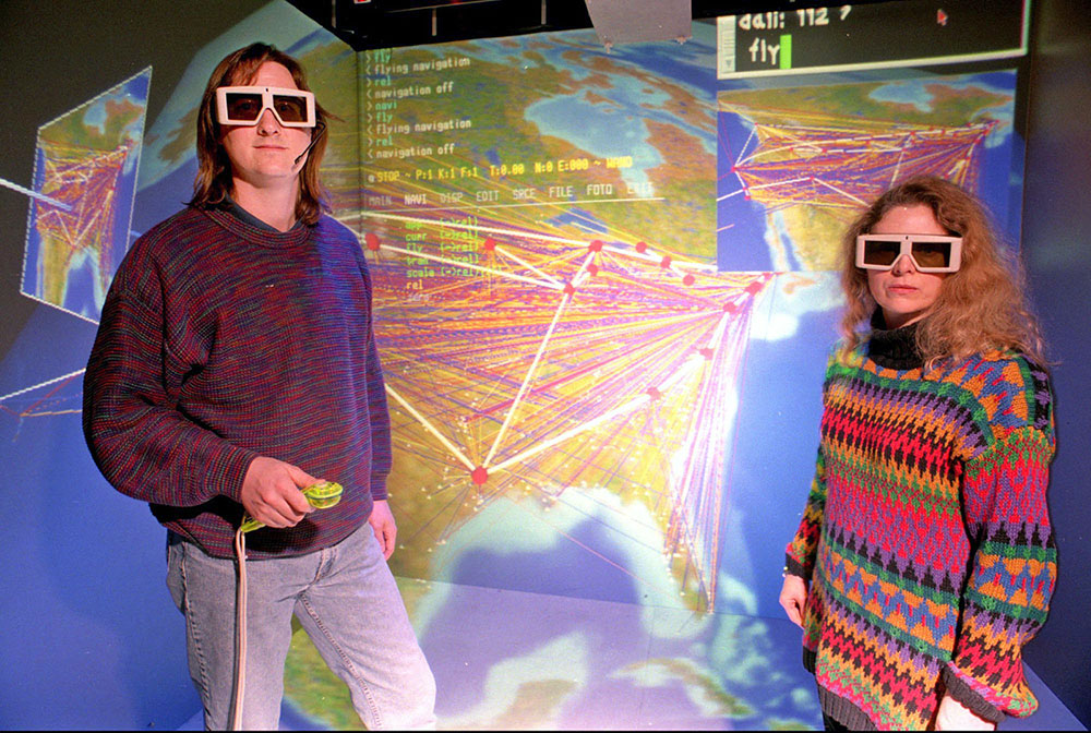 Researcher wearing dark glasses stand in front of a simulation screen.