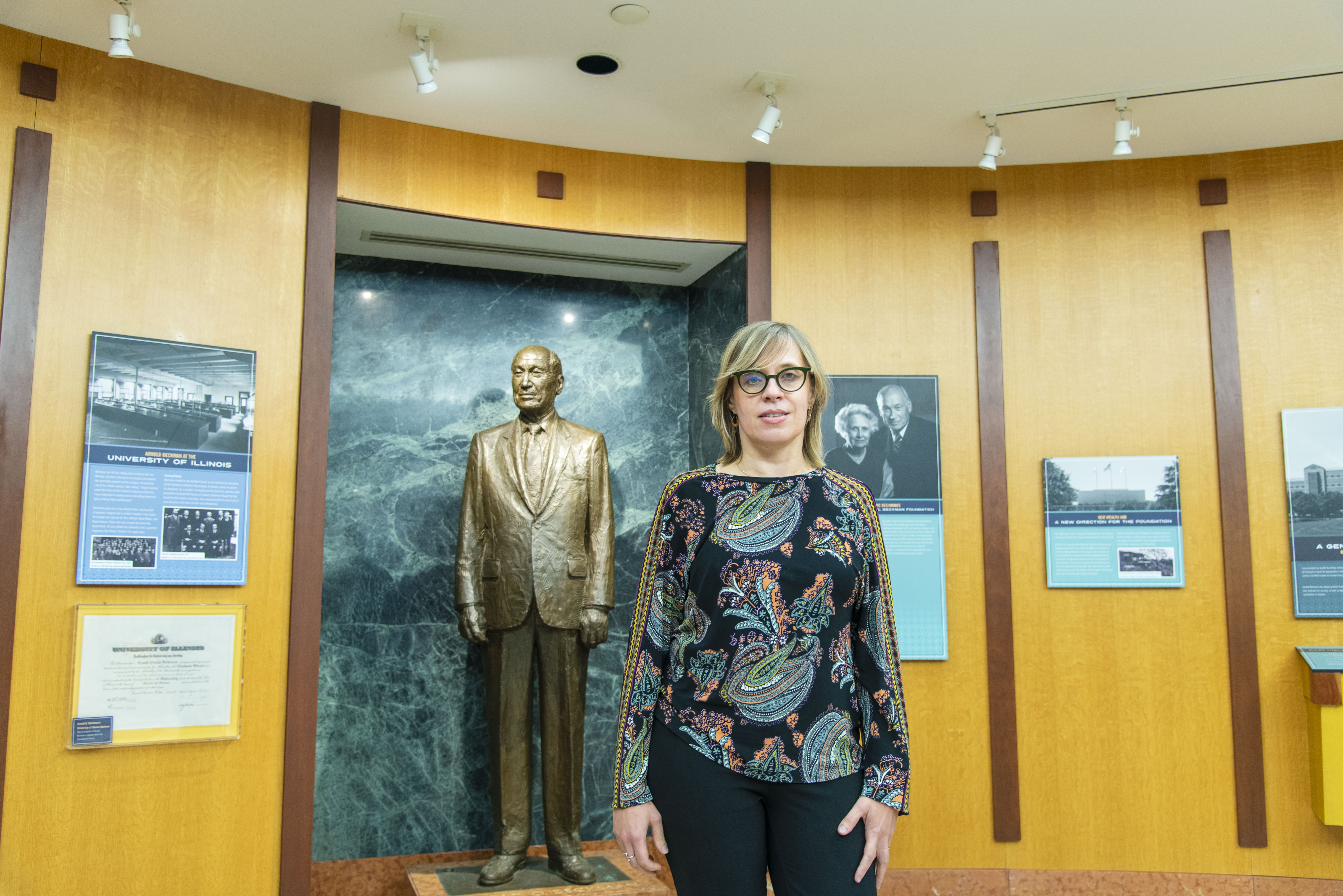 Luisa Ciobanu stands in front of the statue of Arnold O. Beckman in Beckman Institute.
