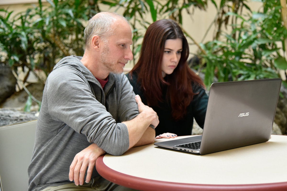 Prof. Aaron Benjamin with graduate student Jessica Siler review notes on her laptop in the atrium of the Psychology Building.