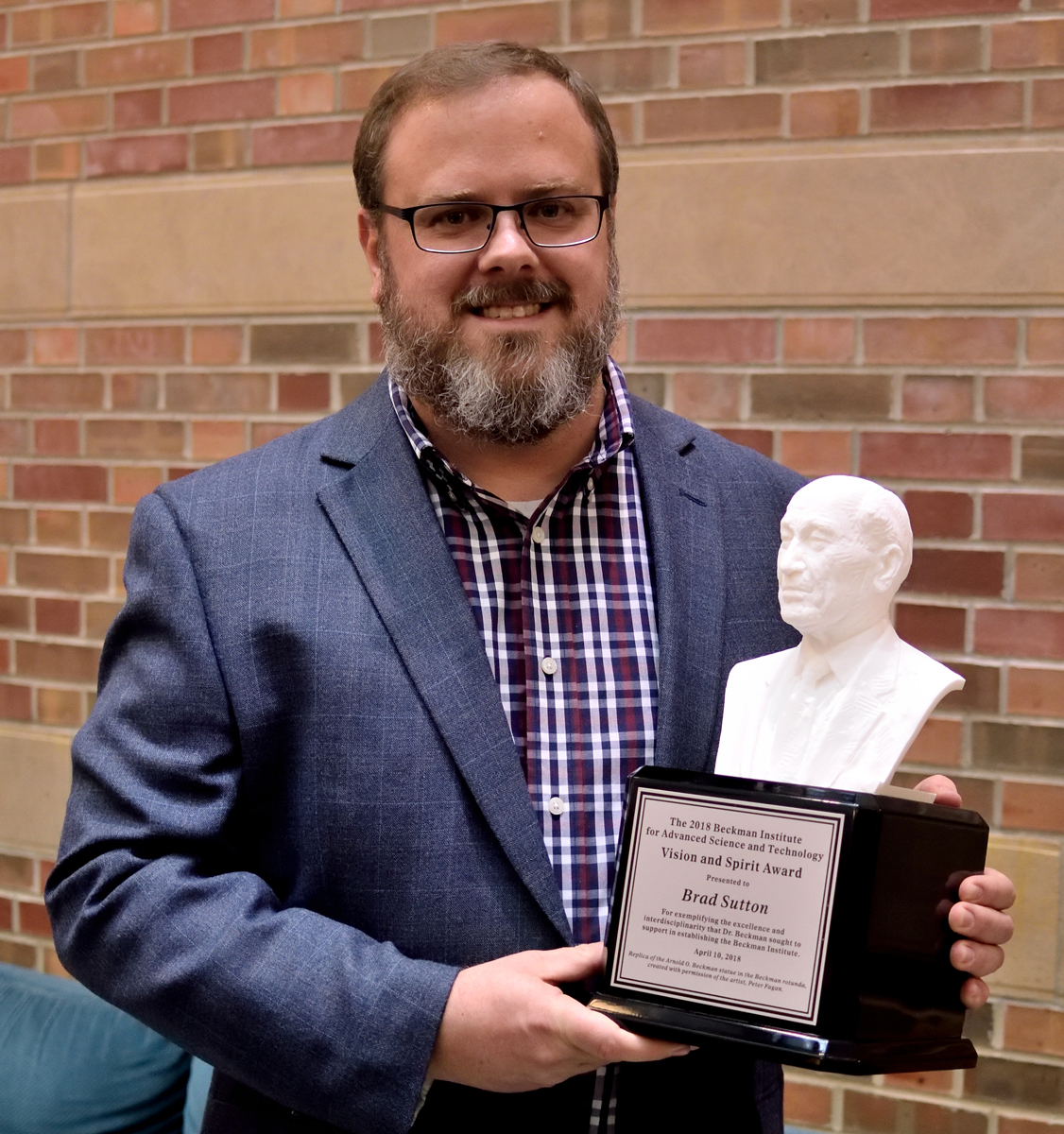 Brad Sutton holding the Beckman Vision and Spirit Award which is a 3D print of a bust of founder Arnold Beckman.