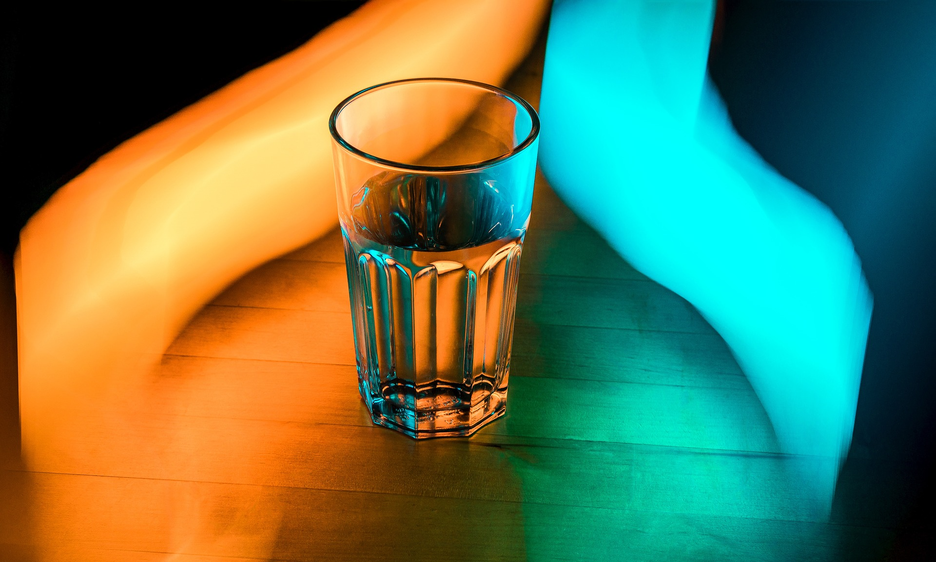 A glass of water sits on a wooden surface in between glowing orange and blue trails of light
