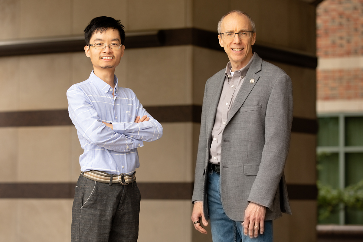 Jeffrey Moore and Yun Liu stand side by side in front of Beckman Institute.