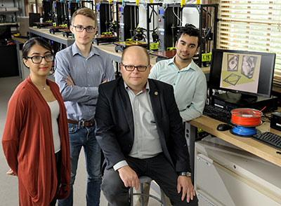 Professor Wawrzyniec Dobrucki (second from right) is joined by PhantomCOR team members Hiba Shahid, Pierce Hadley, and Craig Soares in the 3D printing lab.