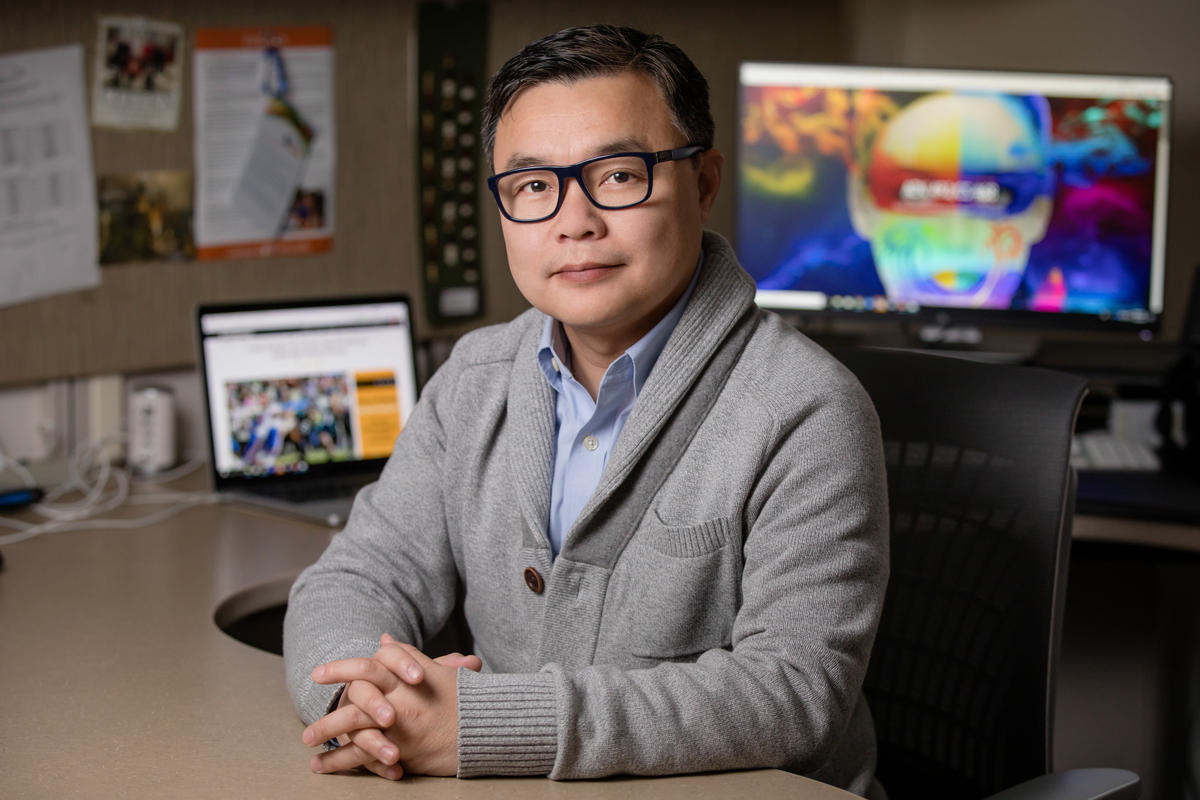 Mike Yao in a gray buttoned sweater and black glasses sits with hands folded in front of computer monitors.