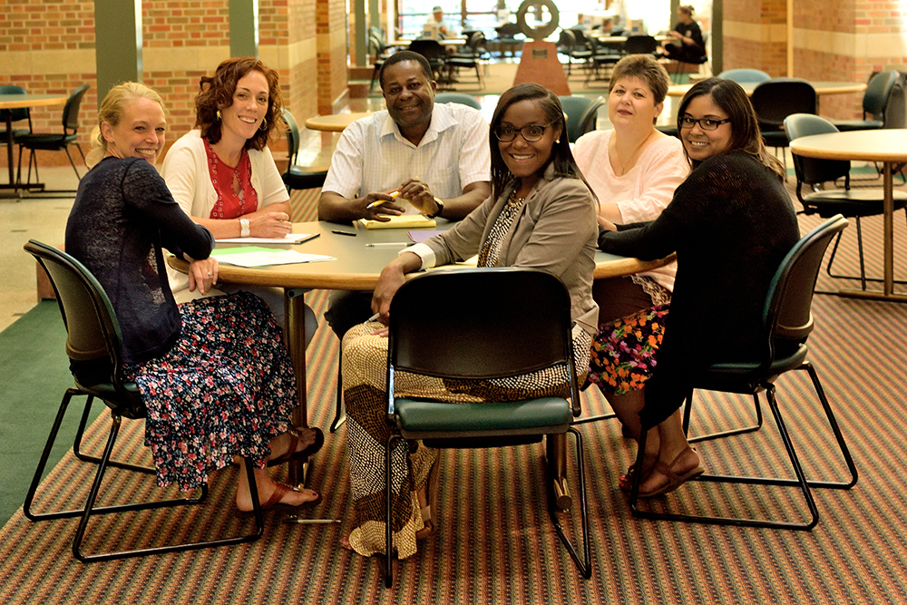 Members of the Beckman Institute Business Office pose in the atrium of the Beckman Institute at the University of Illinois.