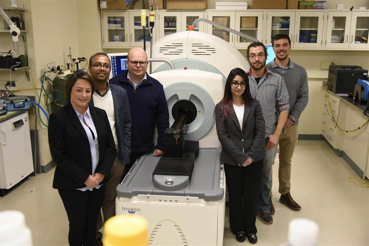 Collaborators pose in front of the Beckman Biomedical Imaging Center's microPET/SPECT/CT scanner.