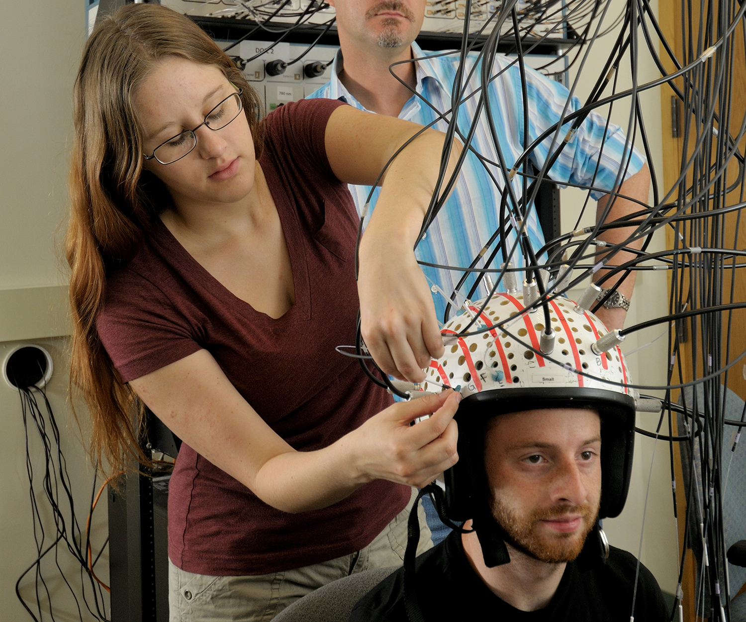 A researcher sets up diffuse optical imaging to measure the brain, which means attaching wires to a cap