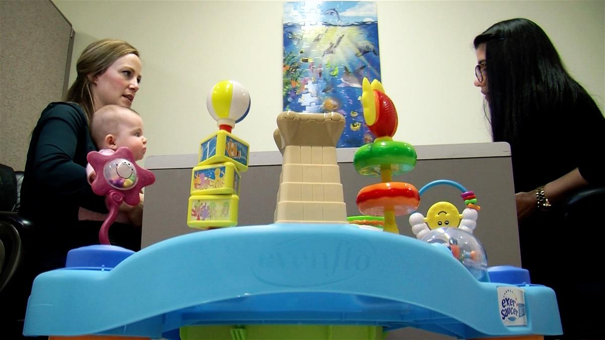 A mom holds a baby while talking to an IKIDS researcher. A baby toy sits in the foreground.