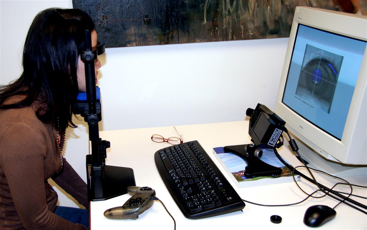 An eye tracker measures a research subject's eyes at the Beckman Institute, while an image of the eyes shows up on the computer monitor opposite.